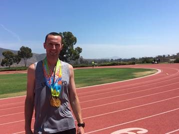 UOPD Officer Anthony Button stands on the track at the 2018 U.S. Police and Fire Championships wearing his age-group medals